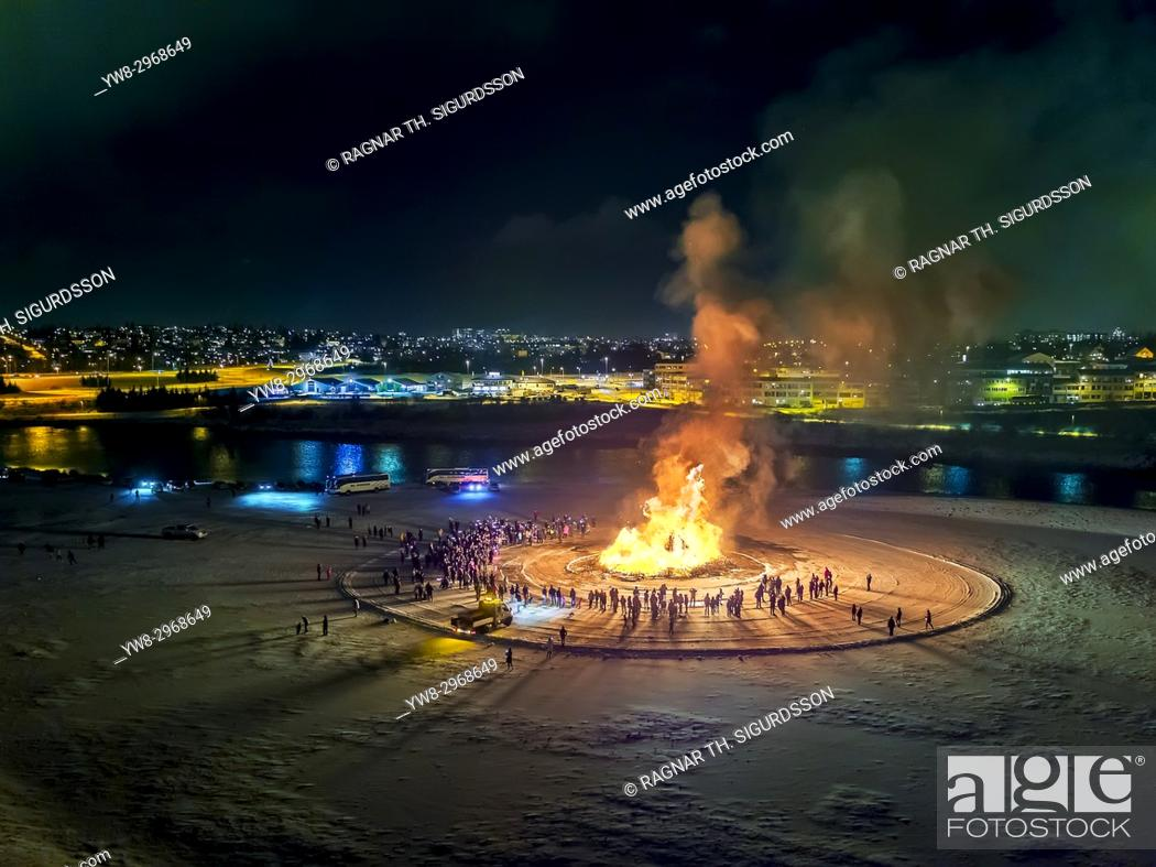 Stock Photo: New Year's Eve Celebration. Bonfires and fireworks on New Year's is an annual event, Reykjavik, Iceland. This image is shot with a drone.