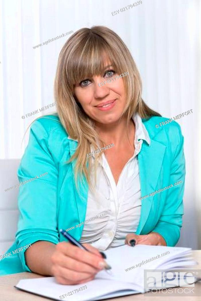 Imagen: Geschäftsfrau schreibt in Terminkalender.