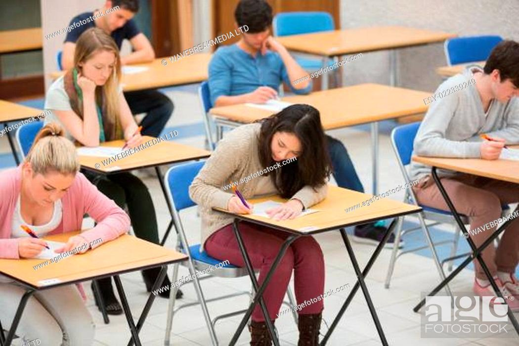 Stock Photo: Students writing in the exam hall of the college.