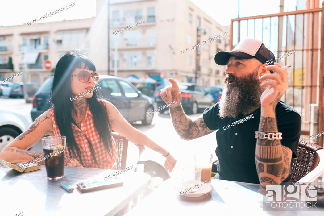 Stock Photo: Mature hipster couple chatting at sidewalk cafe, Valencia, Spain.