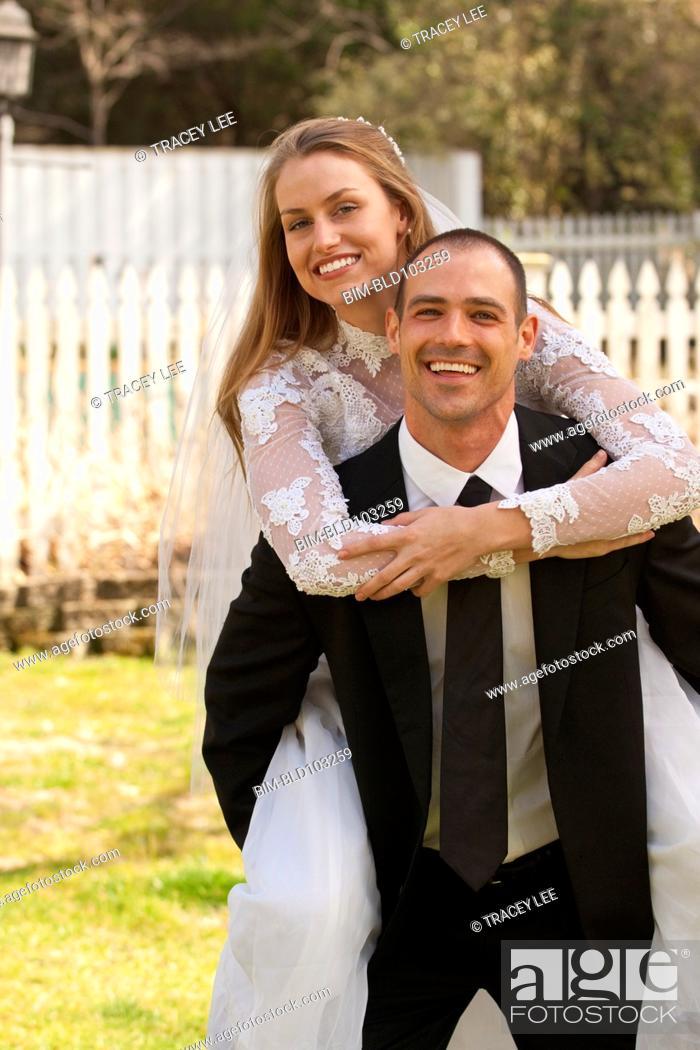 Stock Photo: Caucasian groom carrying bride.