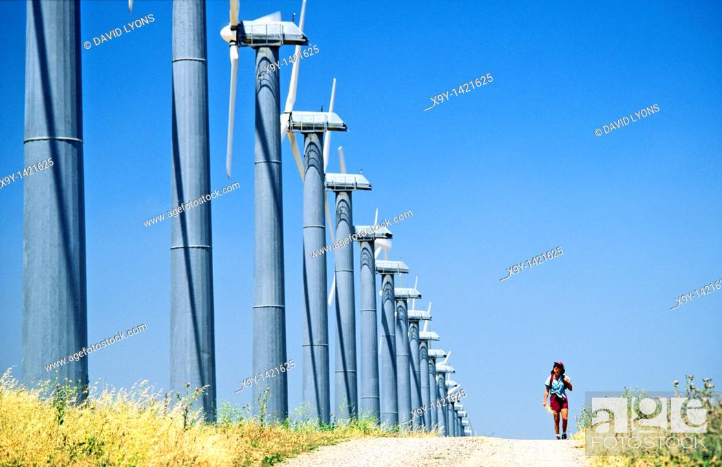 Stock Photo: Wind turbines, part of the massive wind farm complex at Altamont near Livermore, California, USA  Woman walking on track.
