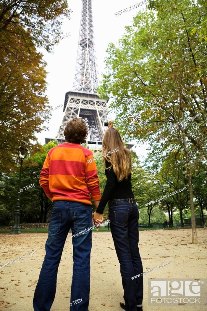 Stock Photo: Rear view of young couple standing under Eiffel tower, Paris, France.