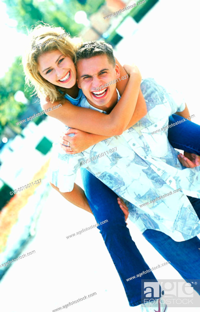 Stock Photo: Young woman riding piggyback on a young man.