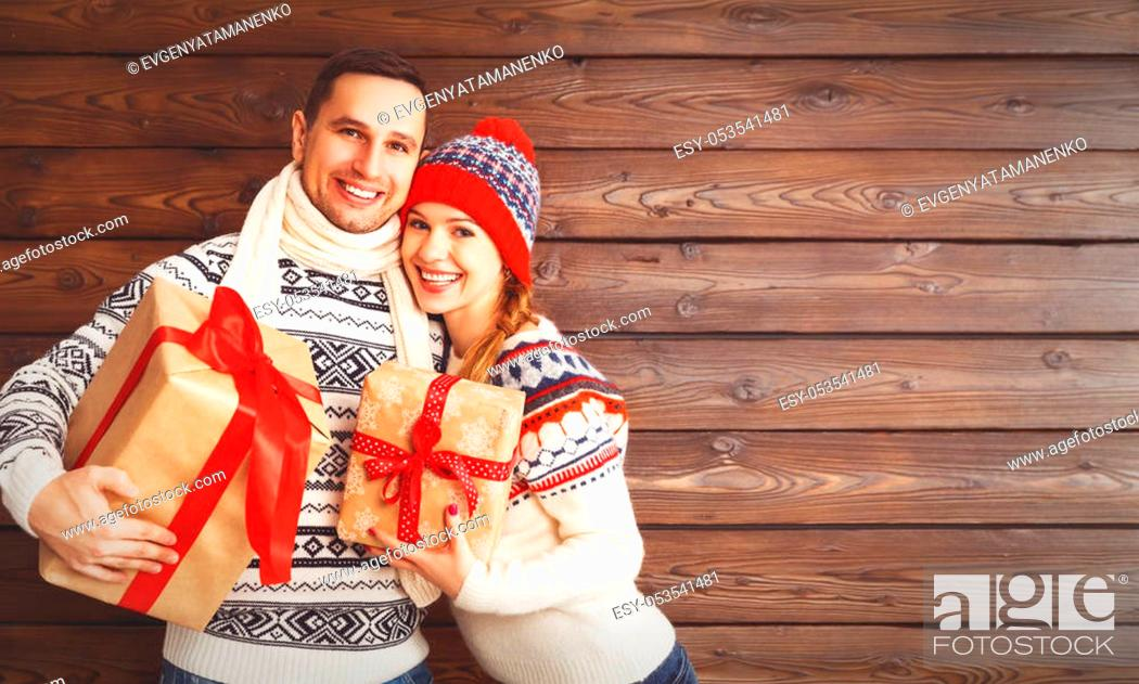 Stock Photo: happy family couple with Christmas gifts in the winter hat on a wooden background.