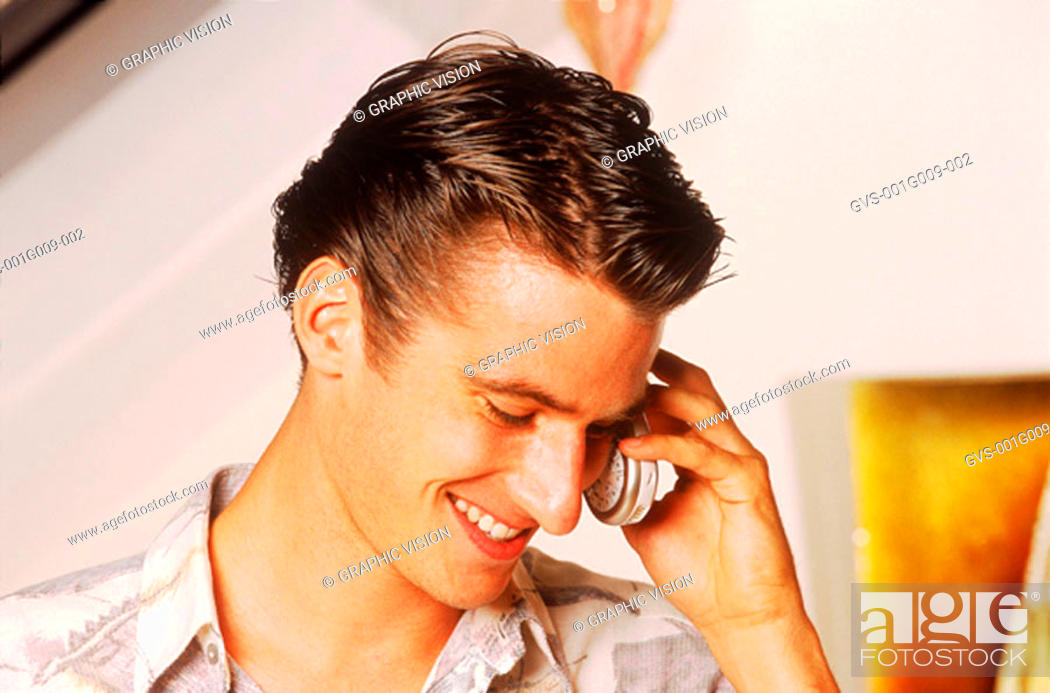 Stock Photo: Young man smiling and talking on a mobile phone.