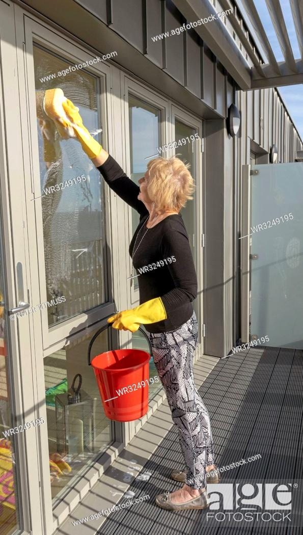Stock Photo: Woman cleaning outside of glass windows using a sponge and a red bucket.