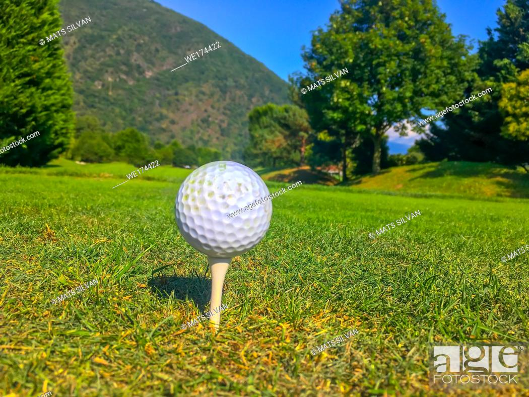 Stock Photo: Golf Ball on Tee on the Fairway with Trees and Mountain in Switzerland.