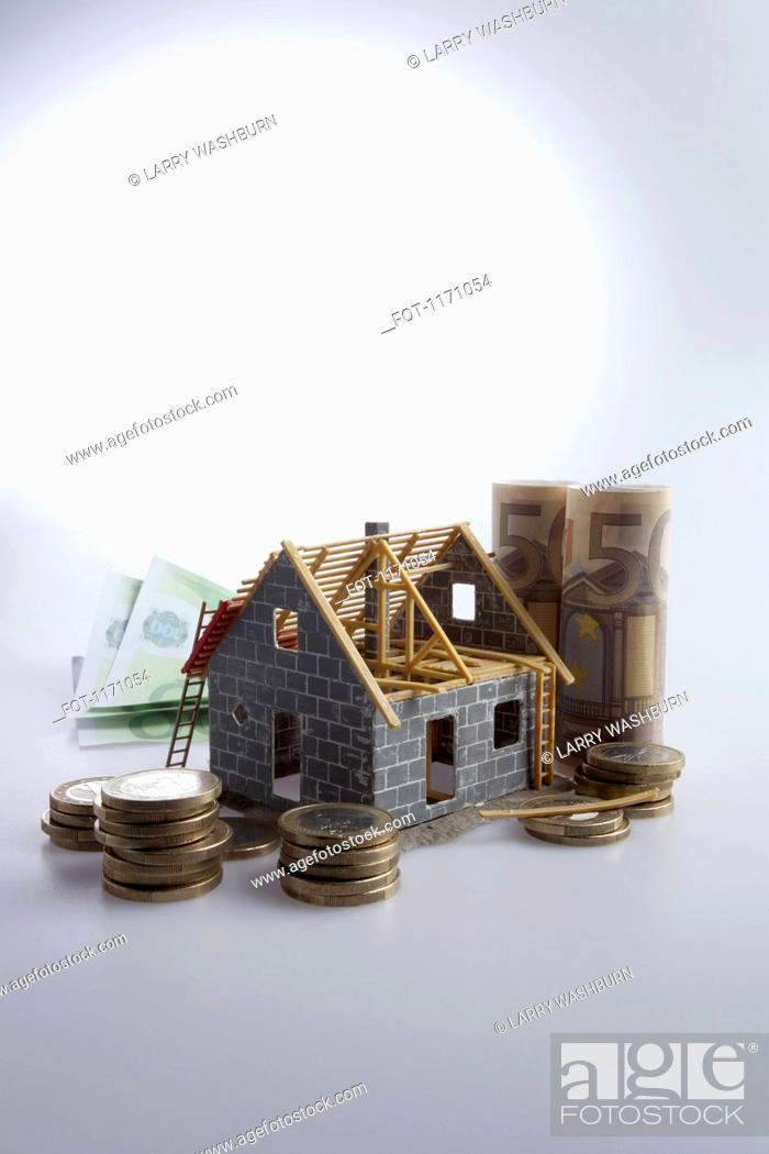 Stock Photo: A partially constructed house with European Union currency and coins around it.