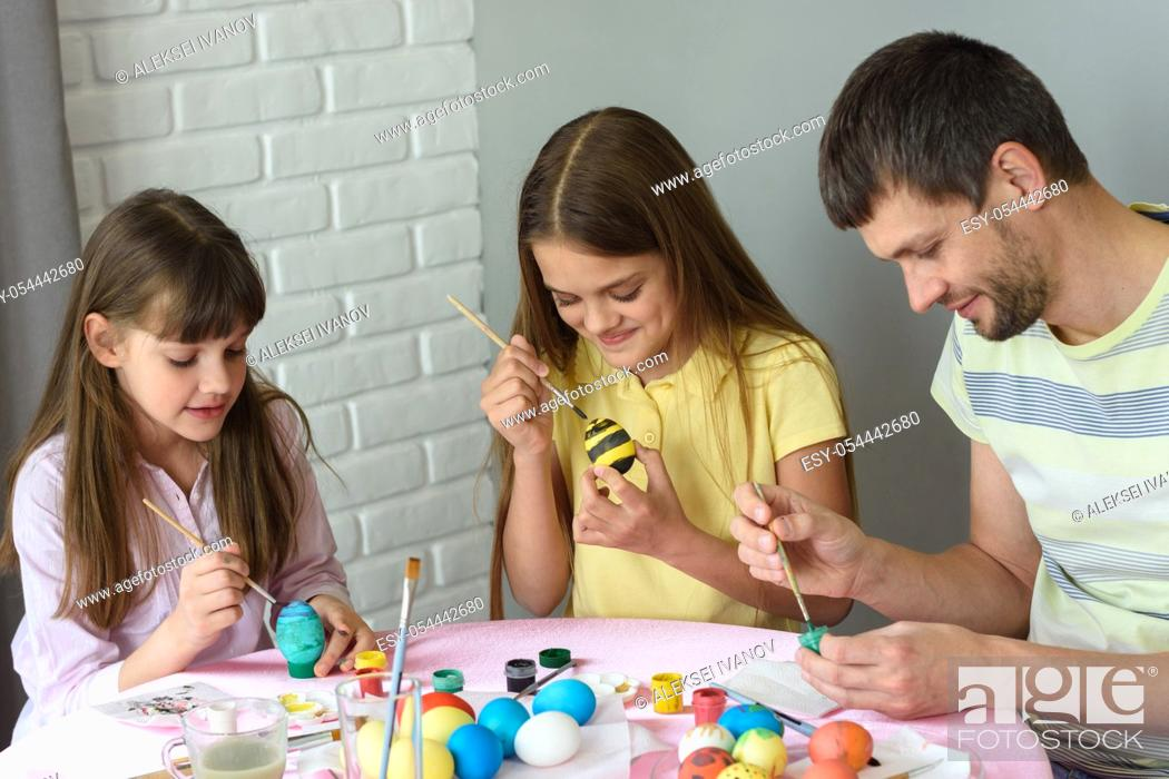 Stock Photo: Dad with two daughters paint eggs for Easter holiday.