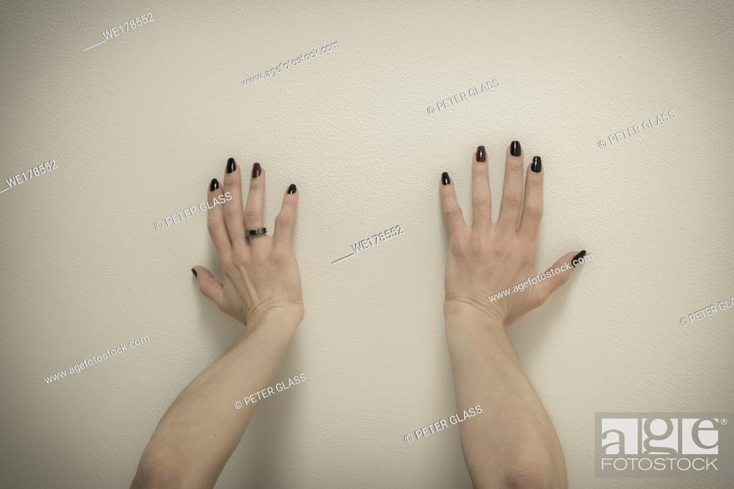 Stock Photo: Young woman's hands, with nail polish on her nails, pushing against the ceiling.