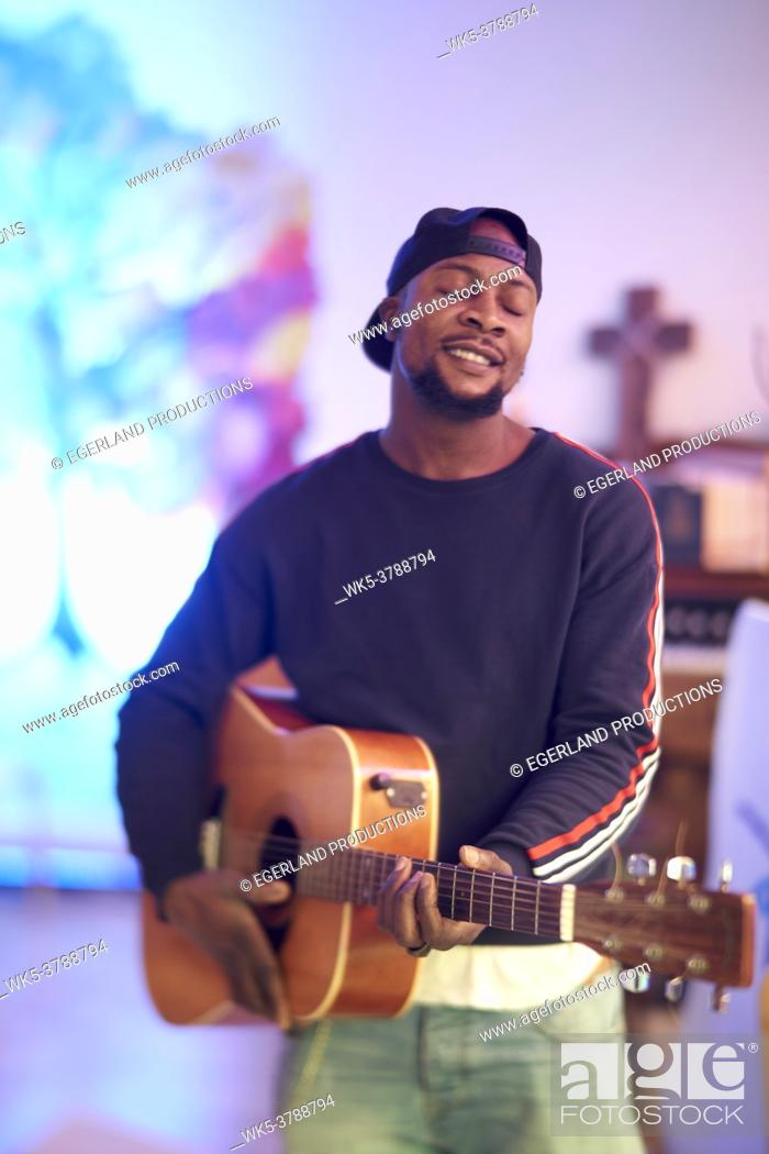 Stock Photo: talented African man feeling his inner creativity and passion, playing acoustic guitar.