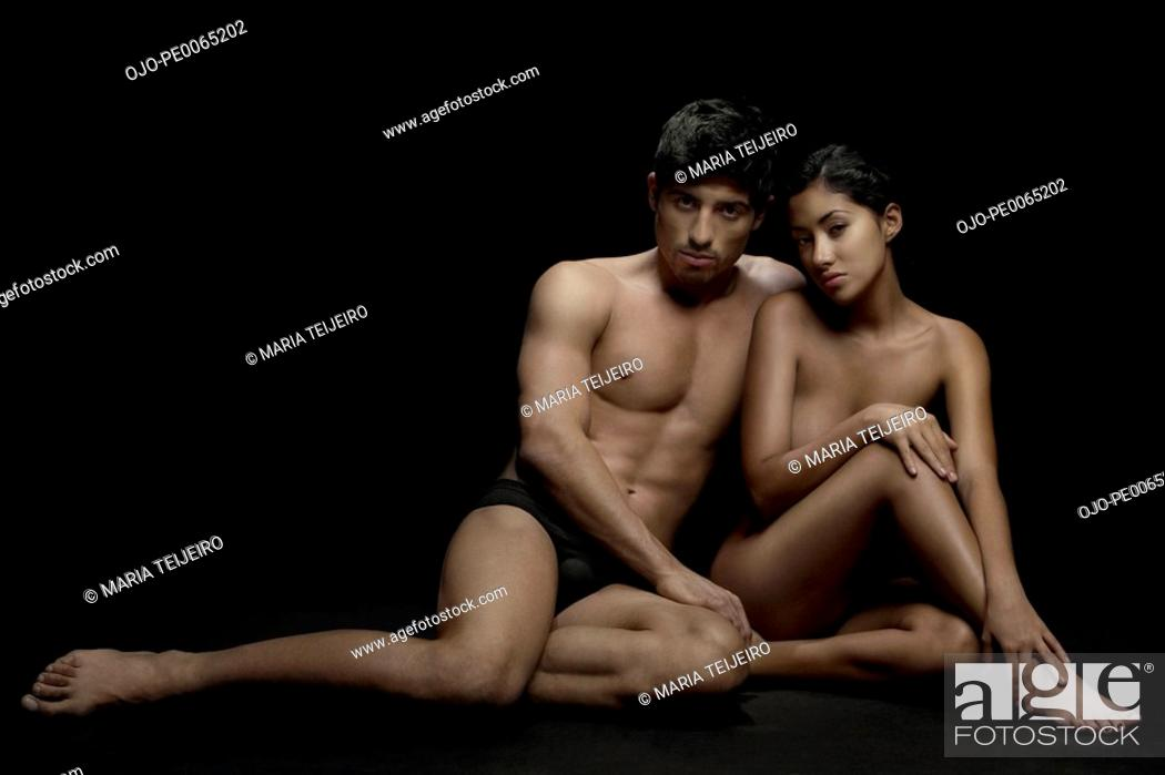 Imagen: Nude couple sitting together.