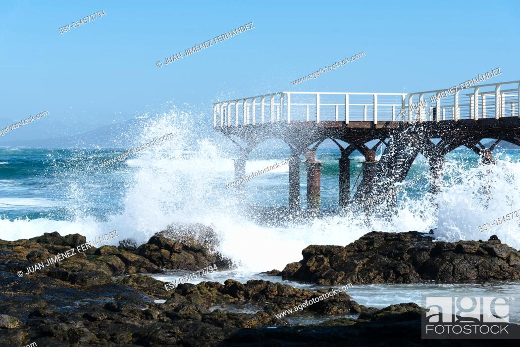Stock Photo: Waves breaking against pier on the beach of Corralejo at morning against blue sky.