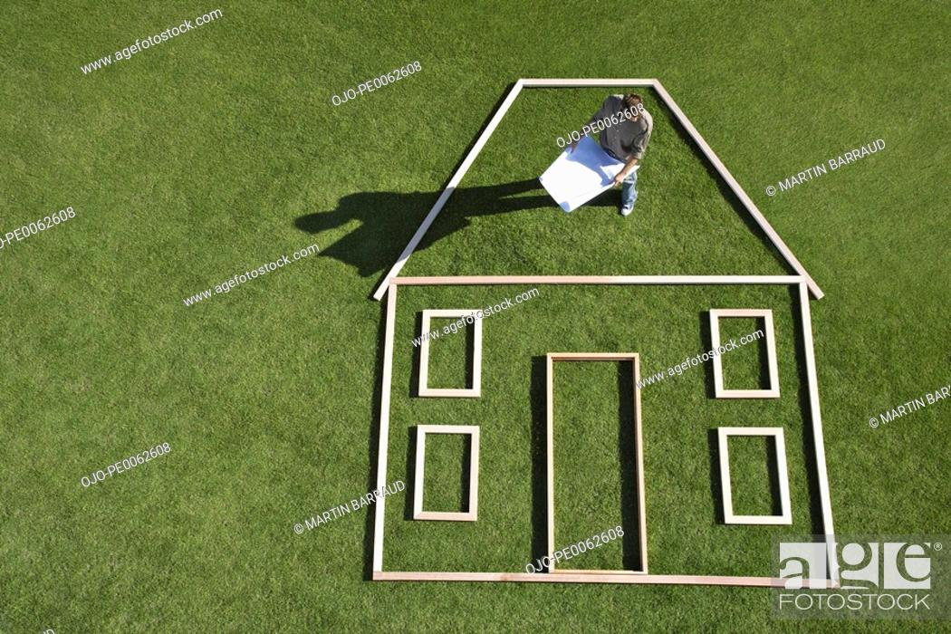 Stock Photo: Architect with blueprints standing inside house outline.