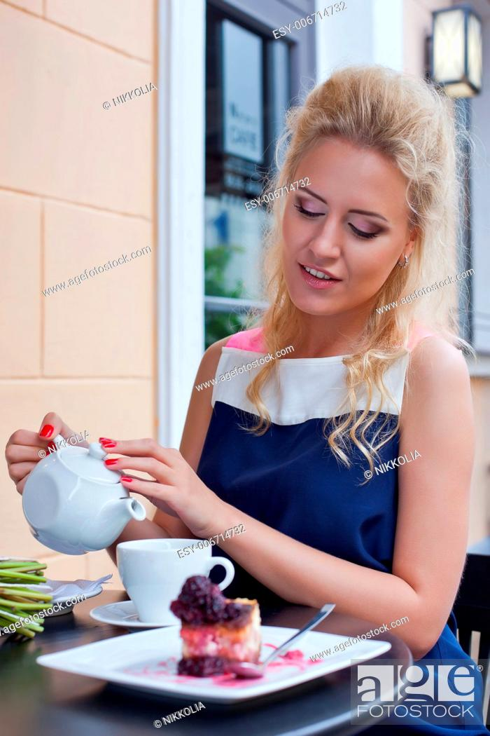Stock Photo: a beautiful young blond girl in summer dress at the table in pavement cafe is going to pour tea from the teapot into the cup.