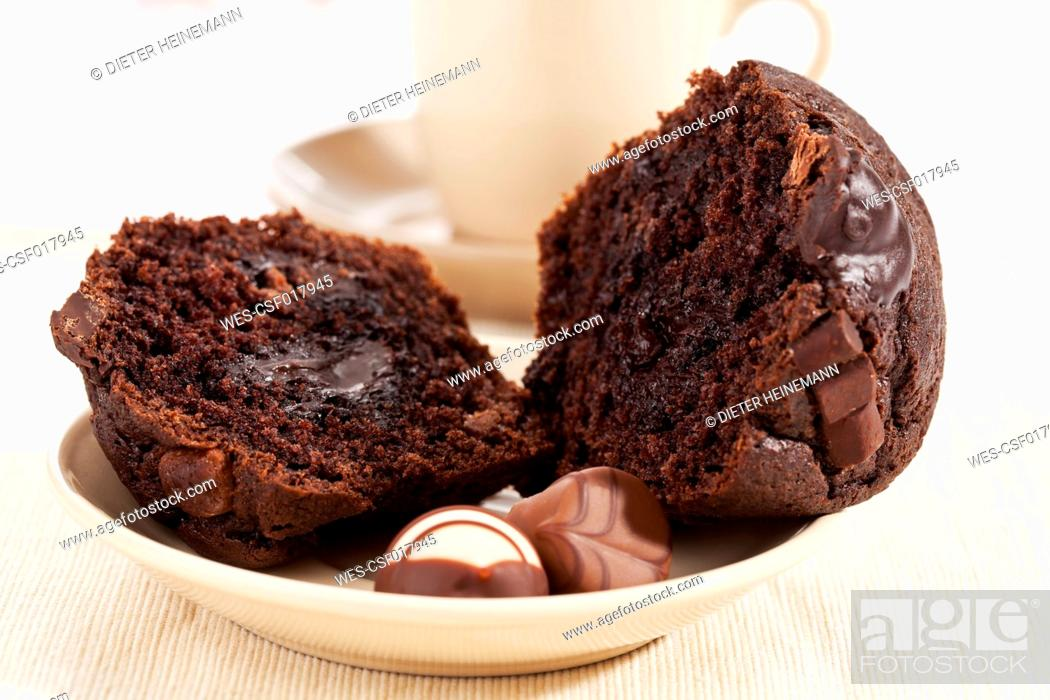 Stock Photo: Plate of chocolate muffin with praline, coffee cup in background.