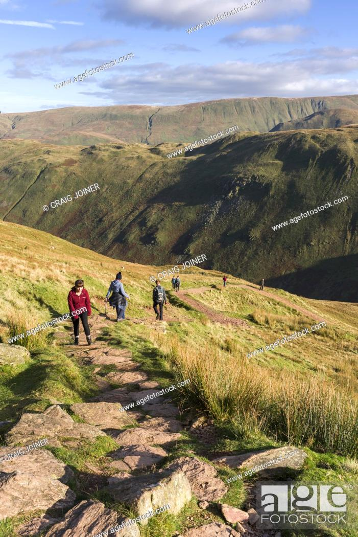 Stock Photo: Walkers on Place Fell with Beda Fell and Wether Hill beyond in the Lake District National Park, Cumbria, England.