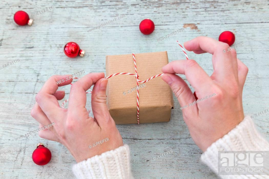 Stock Photo: Woman's hands wrapping Christmas present.