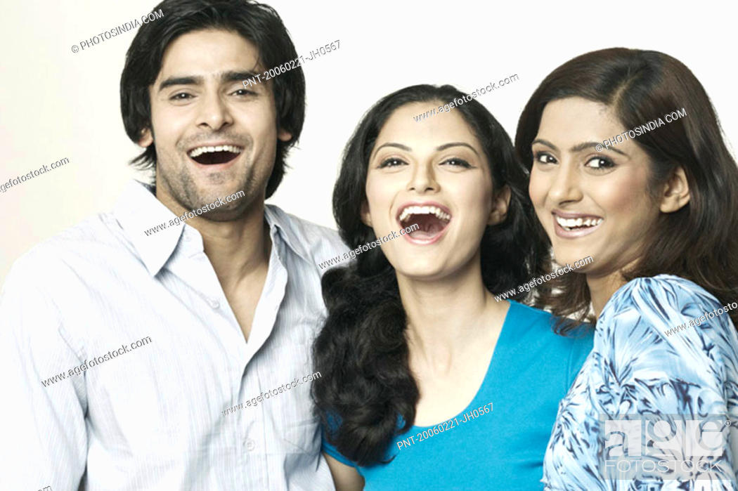Stock Photo: Portrait of two young women and a young man laughing.