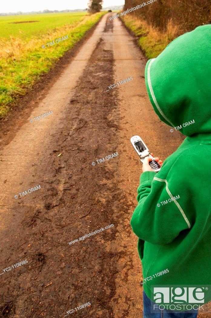 Stock Photo: A child wearing a hoodie texting on his mobile phone on a farm track in Suffolk , England , Britain , Uk.