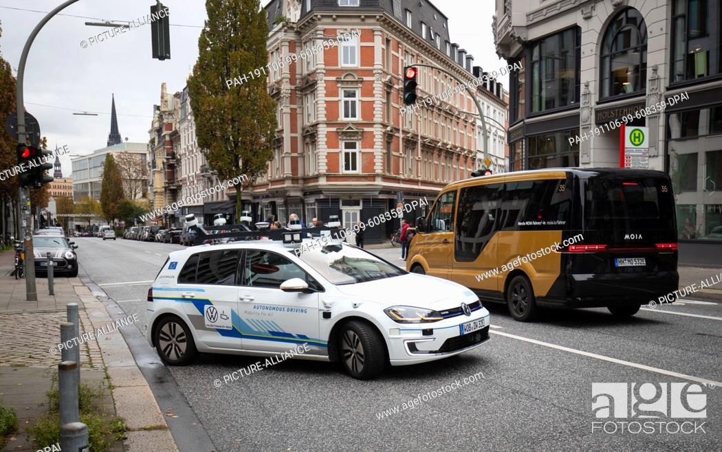 Stock Photo: 06 November 2019, Hamburg: An electric Golf (l), equipped with laser scanners, cameras, ultrasonic sensors and radar for fully automatic driving.