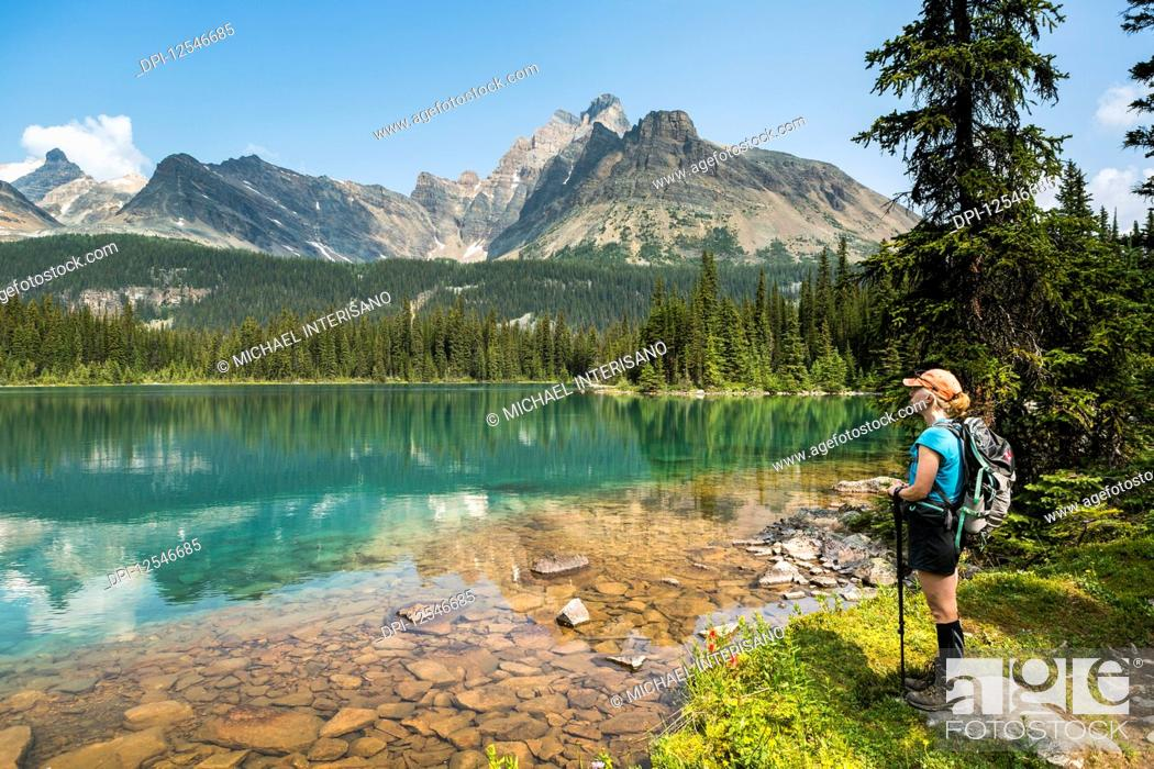 Imagen: Female hiker standing along the shoreline of an alpine lake refelcting mountain range with blue sky; British Columbia, Canada.
