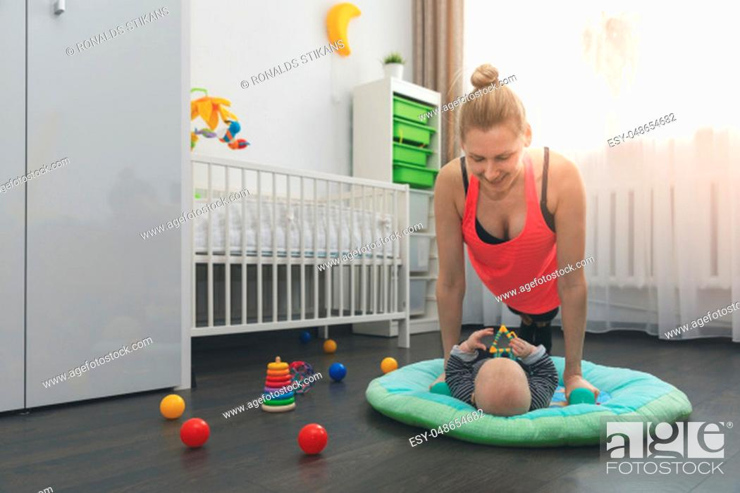 Stock Photo: young woman doing push ups at home while playing with her little baby.
