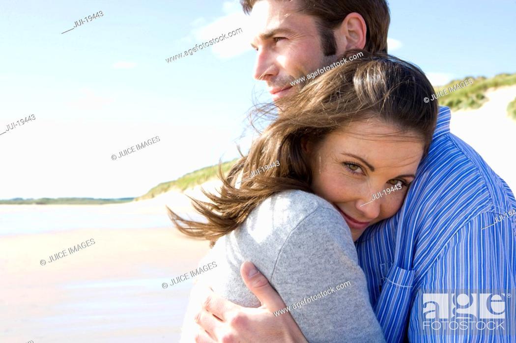 Stock Photo: Couple embracing on beach.
