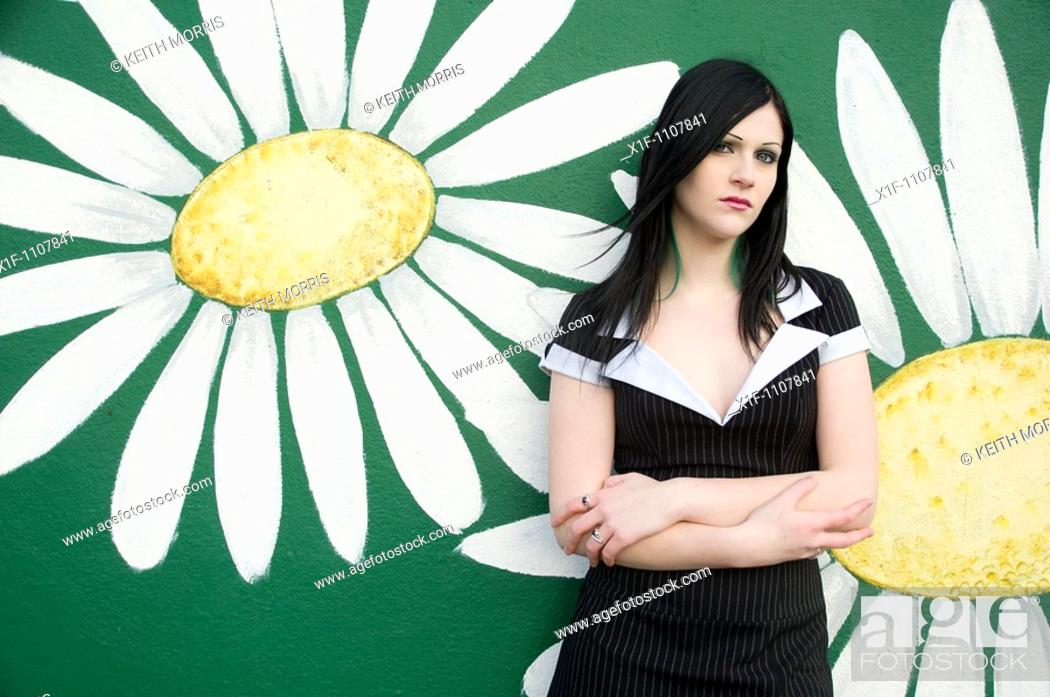 Stock Photo: an attractive teenage girl with long black hair stabding against a wall with flowers painted on it.
