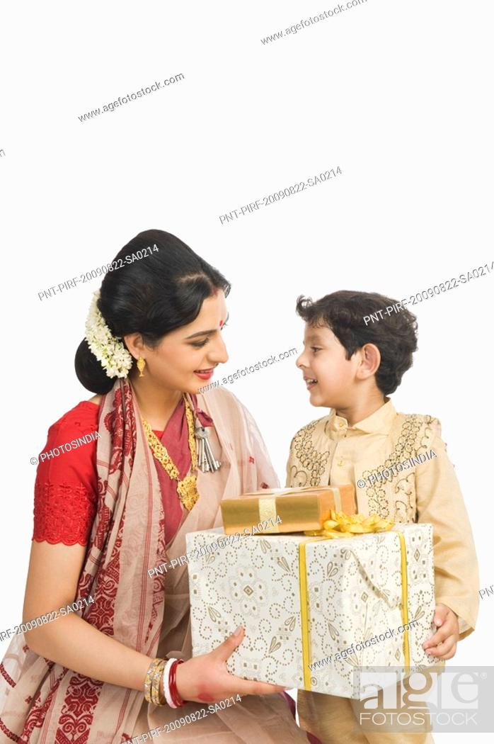 Stock Photo - Woman holding gifts with her son at Durga Puja