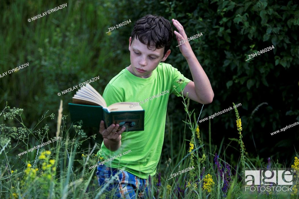 Stock Photo: Russia. Belgorod region. Solomino village. The boy in the meadow with a book.