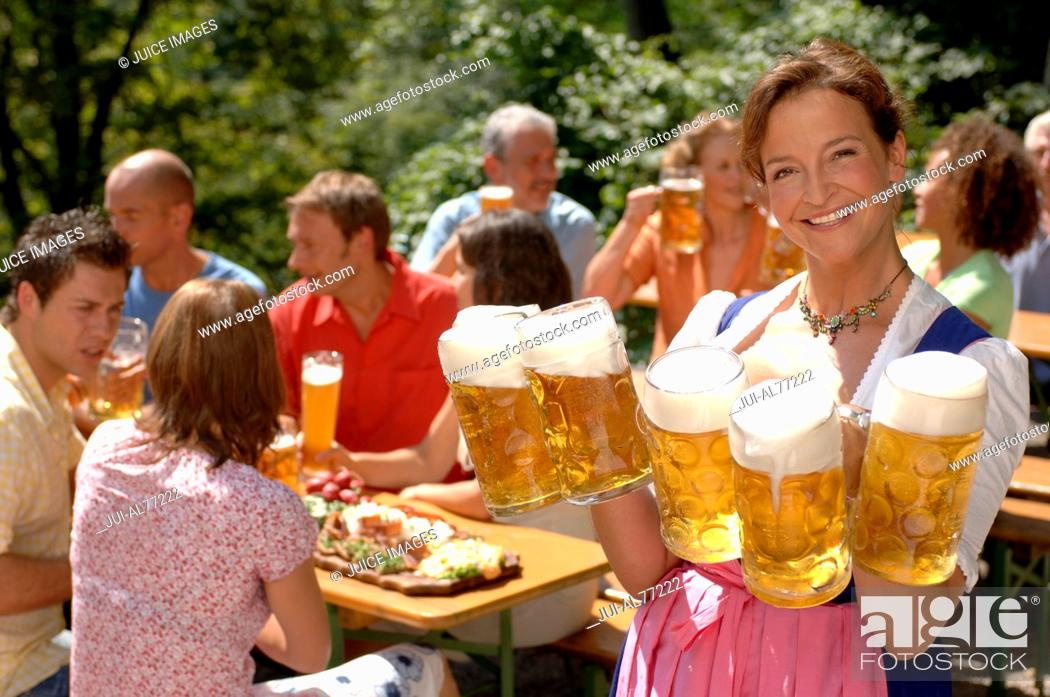 Stock Photo: View of a young woman serving beer, beergarden, Munich, Bavaria, Germany.