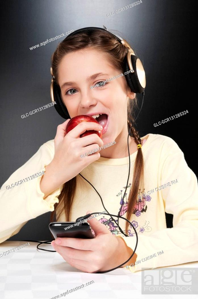 Stock Photo: Close-up of a girl listening to music and eating an apple.