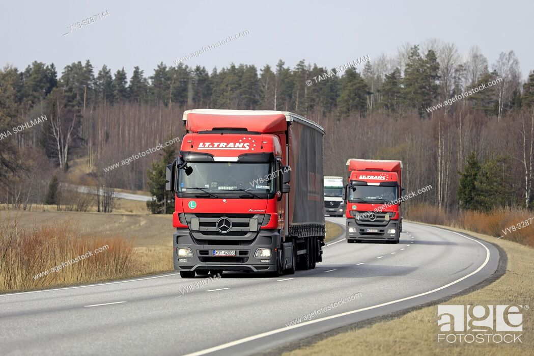 Stock Photo: Salo, Finland - April 5, 2019: Fleet of Mercedes-Benz Actros semi trailer cargo trucks transporting goods along road in Finland on a day of spring.