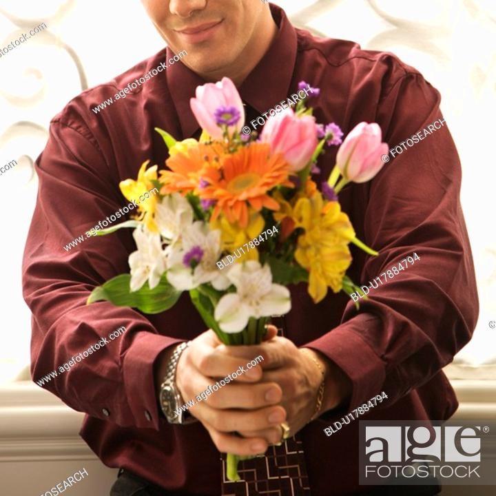 Stock Photo: Man holding bouquet of flowers.