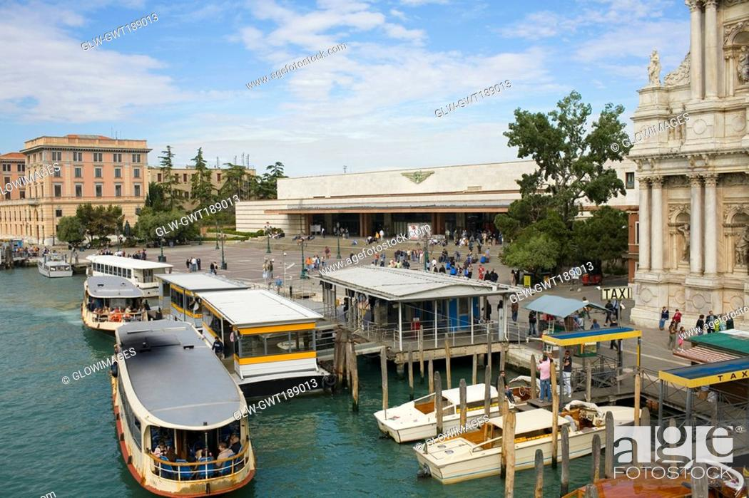 Stock Photo: Gondolas docked in a canal in front of a railway station, Venice, Italy.