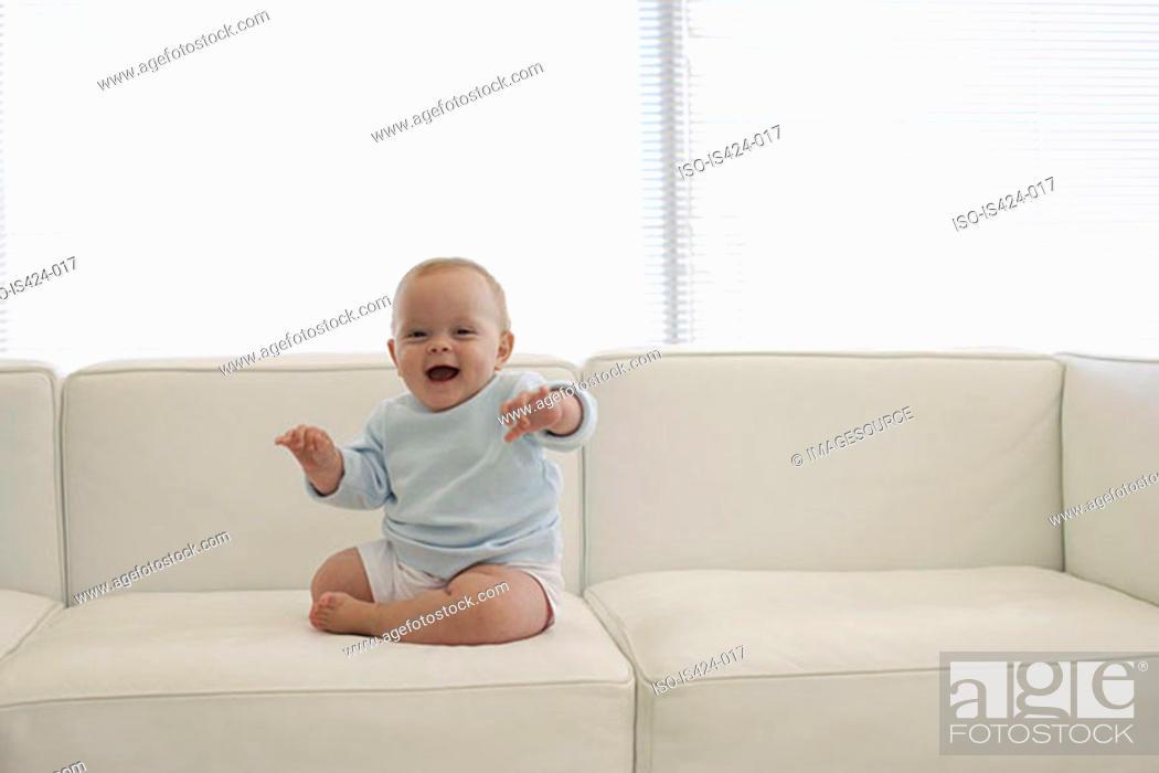 Stock Photo: Baby sat on sofa.