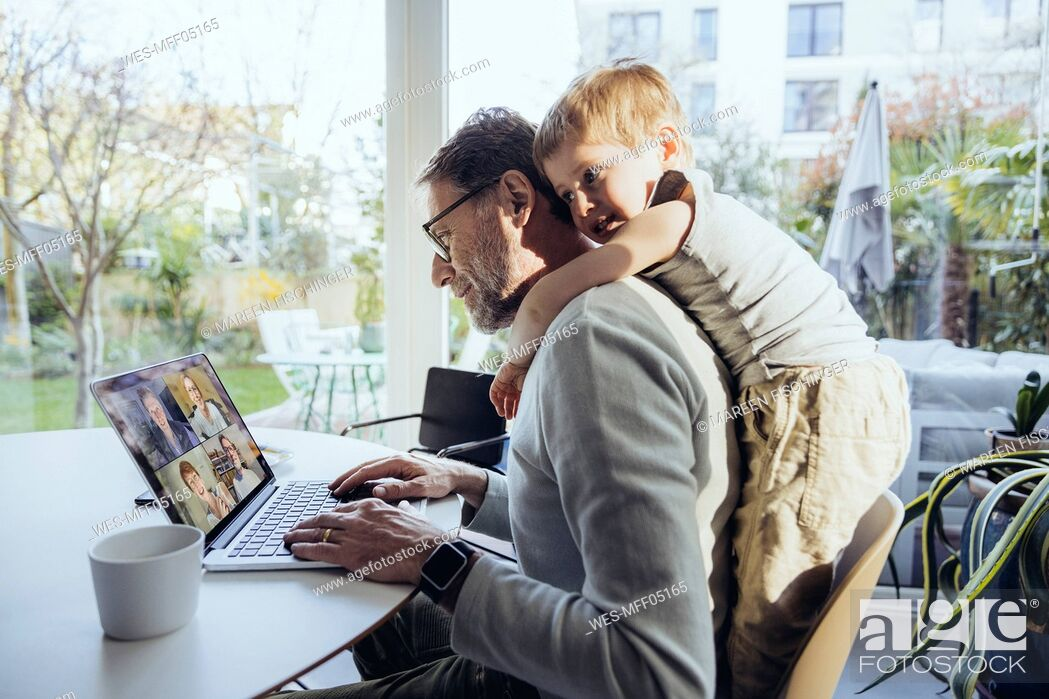 Photo de stock: Little boy hugging father from behind, while working from home.