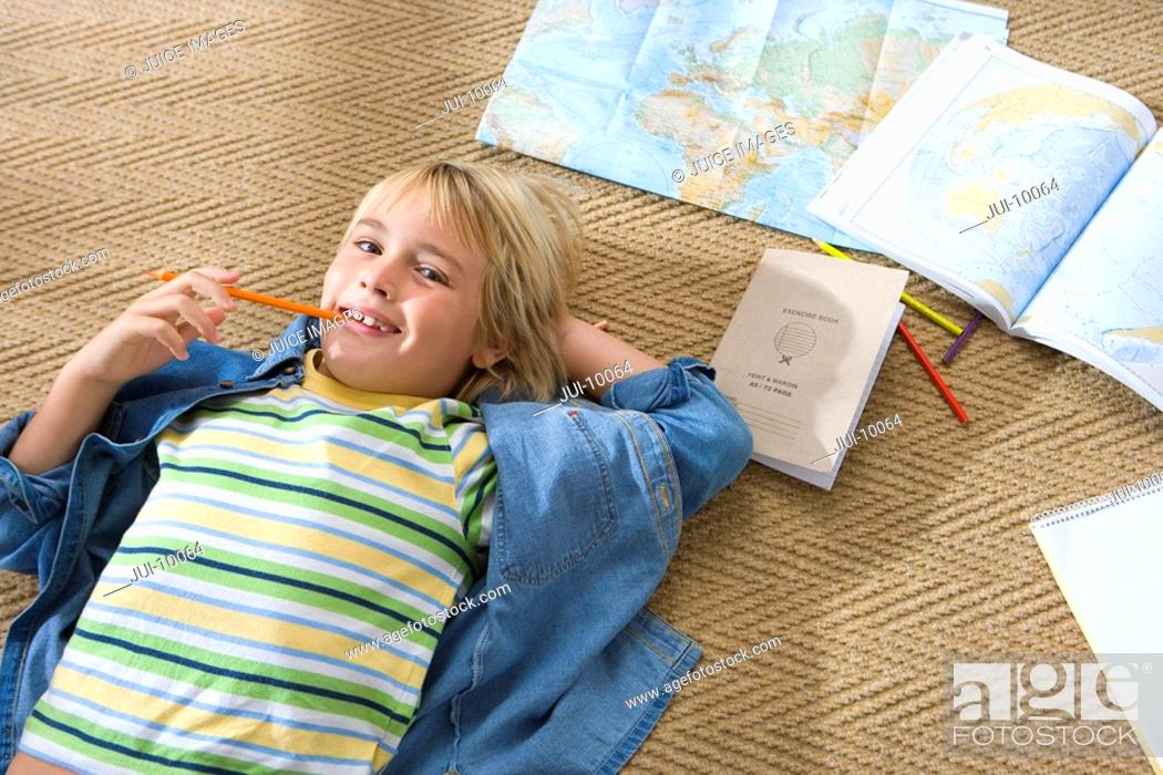 Stock Photo: Boy 6-8 lying on floor by maps, pencil in mouth, smiling, portrait, elevated view.