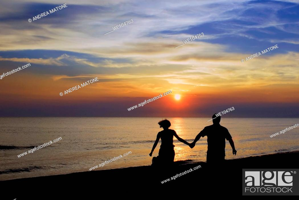 Stock Photo: Romantic couple walking holding hands at sunset.