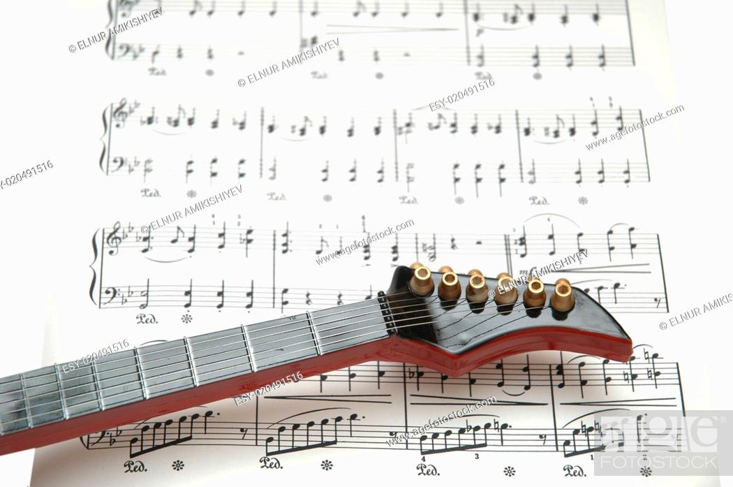 Stock Photo: Rock guitar over the sheet of printed music.