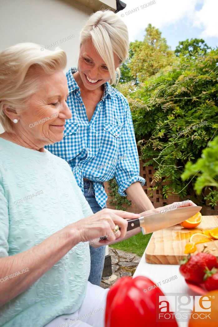 Imagen: Grandmother and granddaughter chatting while preparing food at garden table.