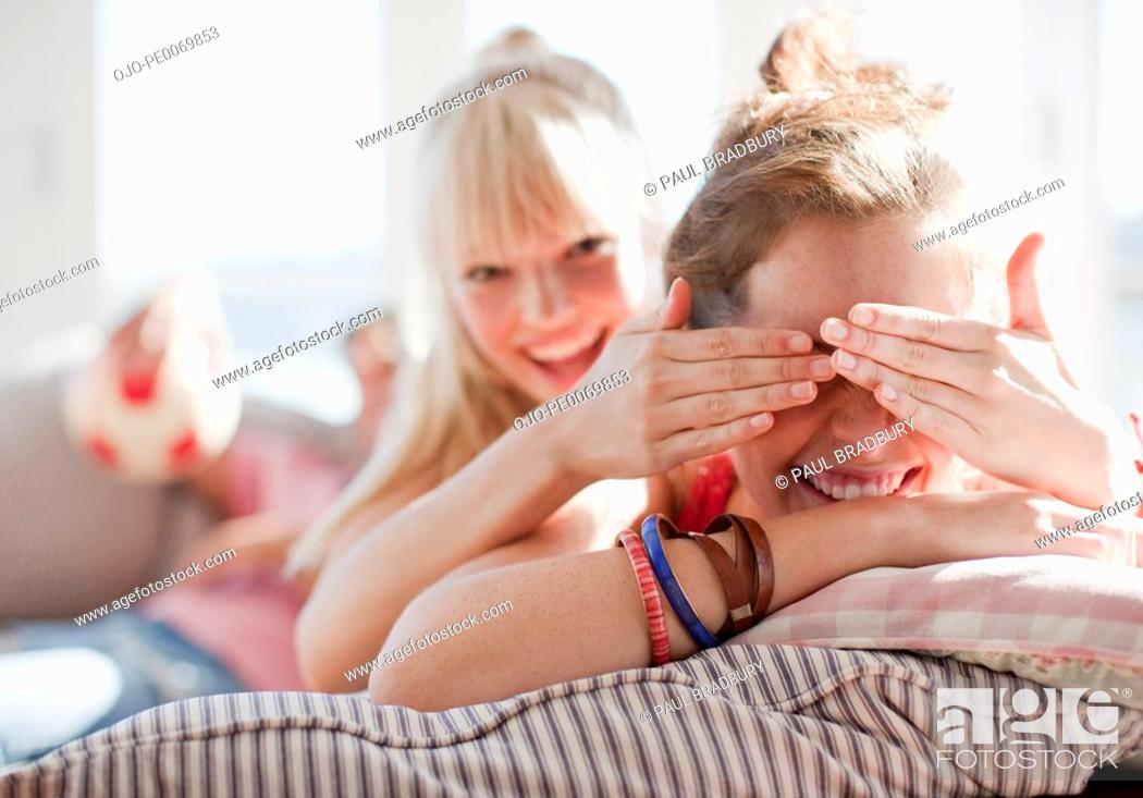 Stock Photo: Woman covering friend's eyes.