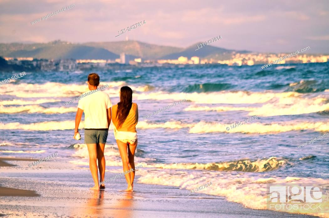 Stock Photo: Couple on the beach walking back. Costa Daurada, Costa Dorada, Catalonia, Spain.