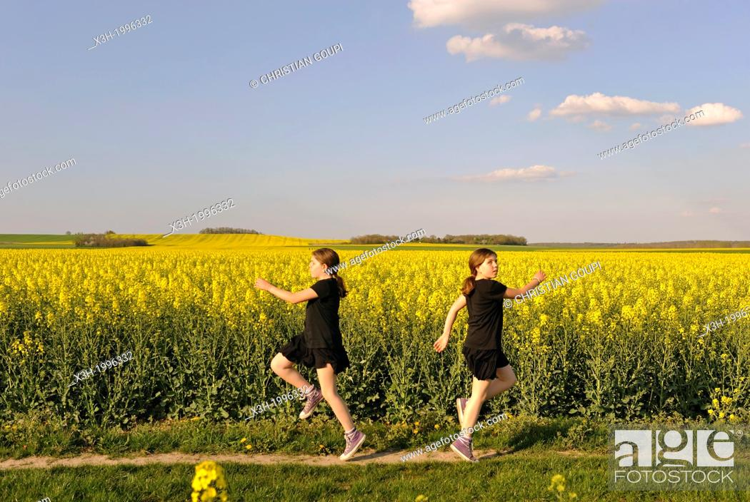 Stock Photo: montage, little girl running in blossoming fields of rapeseed, Senantes, Eure-et-Loir department, Centre region, France, Europe.