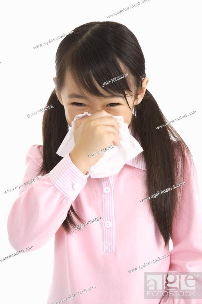 Stock Photo: Little girl blowing nose with tissue.