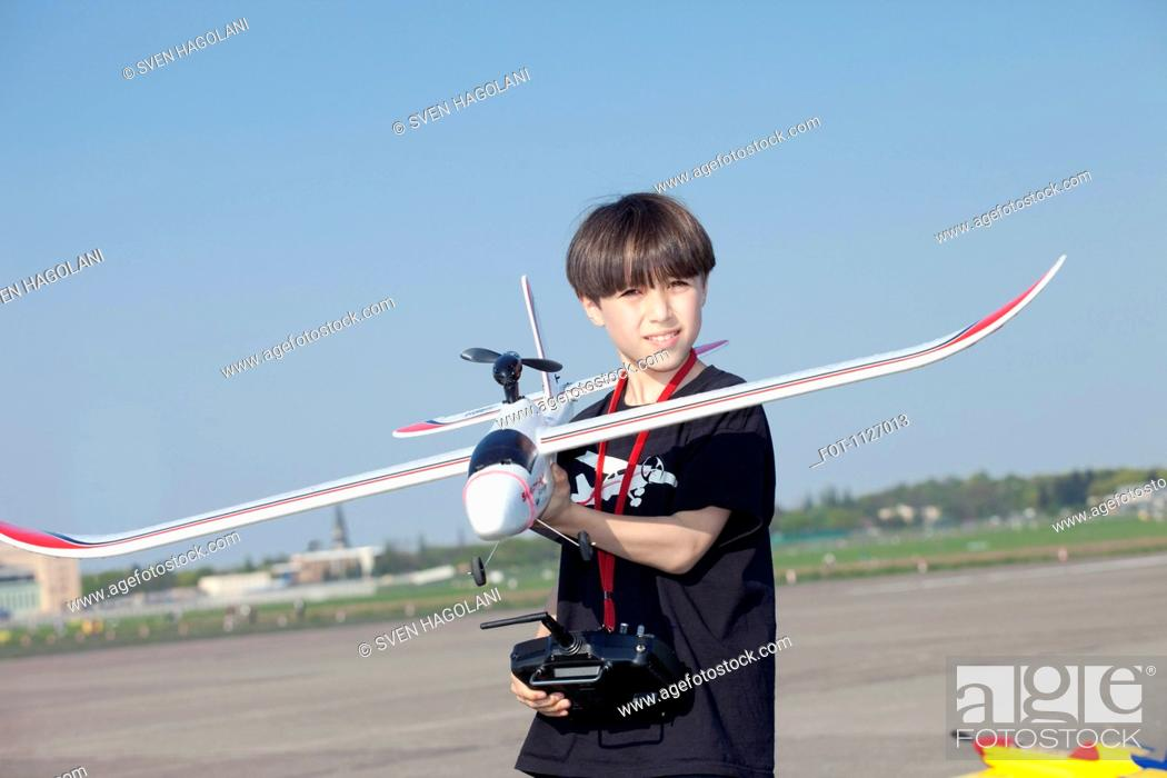 Stock Photo: Boy with model airplane at the abandoned airfield at Tempelhof Airport, Berlin.