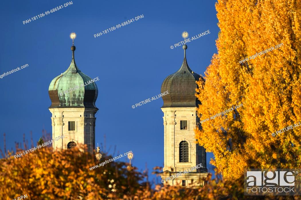 Stock Photo: 06 November 2018, Baden-Wuerttemberg, Friedrichshafen: The two bell towers of the castle church can be seen behind autumn-coloured trees.