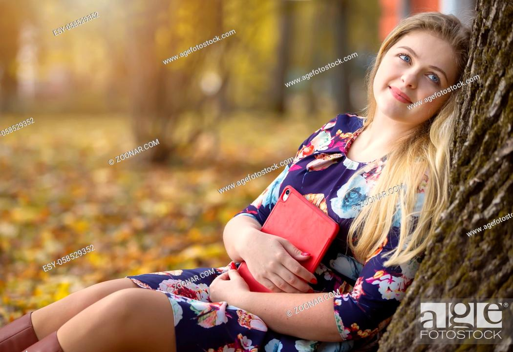 Stock Photo: Pensive dreamy girl in an autumn park sits near a tree with a tablet.